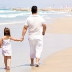 Girl-holding-daddys-hand-while-walking-on-the-beach-150x150